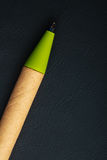 Green pen writing material on black leather background Stock Photos