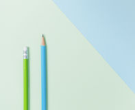 Green pencil and blue pencil on green and light blue background. Stock Images