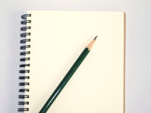 Green pencil on a notebook Stock Photo