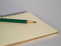 Green pencil on a notebook Stock Photography