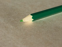 Green pencil over paper Royalty Free Stock Photography