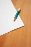Green pencil on paper. Paper and pencil over the desk Royalty Free Stock Images