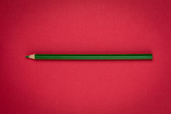 Green pencil on red paper Stock Images