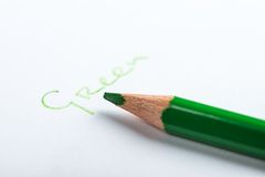 Green pencil on a white paper Stock Images