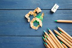 Green pencils with sharpener and shavings. On wooden table Royalty Free Stock Photos