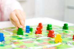 Green people figure in hand of child. red, blue, green wood chips in children play - Board game and kids leisure concept. Board game and kids leisure concept stock photo