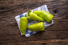 Green peper.Fresh green pepper blue checkered tablecloth on old oak table.  Stock Photo