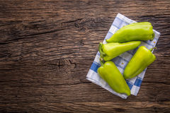Green peper.Fresh green pepper blue checkered tablecloth on old oak table.  Stock Image