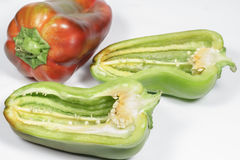 Green pepper cut in half with other one red at background Royalty Free Stock Photos