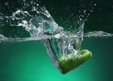 Green pepper falling into water Stock Image