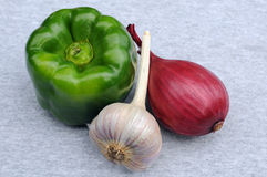 Green Pepper, Garlic And Onion Bulbs. Green sweet pepper, garlic and onion bulbs on grey background Stock Photos