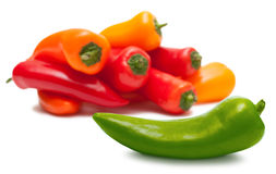 Green pepper, heap of red and orange over white Stock Image