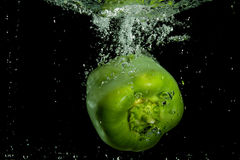 Green pepper plunging in water Stock Image