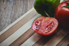 Green pepper and tomato on the cutting board Royalty Free Stock Photos
