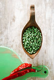 Green peppercorns in bowl and red chillies on green wooden board Royalty Free Stock Photography