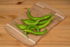 Green peppers on a cutting board. A bunch of green peppers on a wooden surface Stock Photos