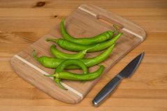 Green peppers on a cutting board with a knife. A bunch of green peppers on a wooden surface Stock Photo