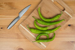Green peppers on a cutting board with a knife, top view. A bunch of green peppers on a wooden surface Stock Image