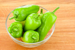 Green peppers in transparent glass bowl on wooden board Royalty Free Stock Image