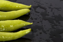 Green peppers on a wet black surface Royalty Free Stock Photography