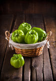 Green peppers in wicker basket. Green peppers in rustic wicker basket on rustic wooden table Royalty Free Stock Images