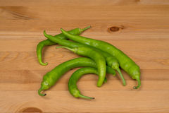 Green peppers on a wooden surface. A bunch of green peppers on a wooden surface Royalty Free Stock Image
