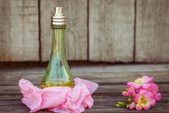 Green perfume bottles near flowers fresia Stock Photo