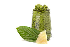 Green pesto in the glass with piece of cheese and leaf of basil Stock Photography