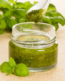 Green pesto in a jar with fresh basil Royalty Free Stock Image