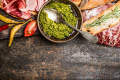 Green pesto and meat plate with bread and antipasti on rustic wooden background, top view, border. Royalty Free Stock Photography