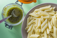 Green pesto pot sauce with white pasta on plate on a green background Stock Images