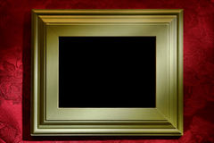Green Picture Frame over Red Wallpaper Background. Green painted wood picture frame with black empty blank space over red damask fabric wallpaper wall background stock photo