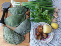 Green pies, dough cooked from nettle. Green dough, stuffed potato, onion and mushrooms. green pastry, cooked from nettle and wild plants royalty free stock images