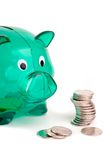 Green Piggy Bank. Green Plastic Savings Piggy Bank And Pile Of Coins, Isolated Over White Stock Images
