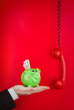 Green Piggy Bank. An executives hand holding a green piggy bank stuffed with money, on a red background Royalty Free Stock Photography