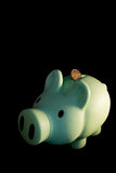 Green piggy bank. In a black background Royalty Free Stock Photos