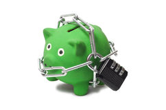 Green Piggy Bank in Chains. Macro of green piggy bank with padlock and chains Royalty Free Stock Photo