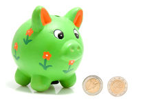 Green piggy bank with coins. Isolated on white background Stock Image