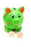 Green piggy bank with coins. Isolated on white background Royalty Free Stock Image