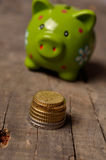 Green piggy bank with coins. Pile of Euro coins in front of a green piggy bank Royalty Free Stock Photos