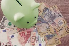 Green piggy bank on different currencies. Piggy bank on Australian dollars, Euros and US dollars on a wooden table Stock Image
