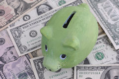 Green piggy bank and dollars. Close up Stock Photos