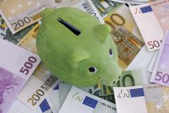 Green piggy bank and euro banknotes. Close up Royalty Free Stock Photo