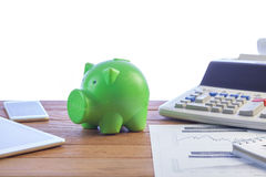 Green piggy bank, finance. Business man putting money coin into green piggy bank, finance and investment concept Royalty Free Stock Photography