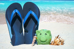 Green piggy bank and Flip Flops. Green piggy bank, Seashells and blue Flip Flops on the Beach Stock Photos