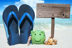 Green piggy bank and Flip Flops. Green piggy bank, Seashells, blue Flip Flops and a wooden Signboard on the Beach Stock Images