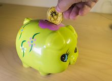 A green piggy bank with a golden bitcoin. Economical and financial concept involving cryptocoins, investment and savings Stock Photo