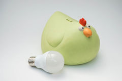 Green piggy bank with LED bulb. In white background Stock Image