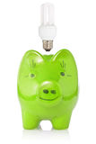 Green piggy-bank with lightbulb. Energy savings concept. Green piggy-bank with compact fluorescent lightbulb Stock Photography