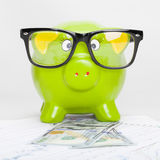 Green piggy bank over stock market chart with 100 dollars banknote - 1 to 1 ratio Stock Image